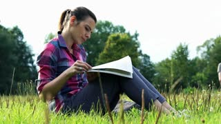 Young woman sitting in park and reading magazine