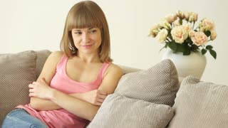 Young woman sitting on a couch and smiling