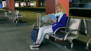 Young woman sitting on platform and reading interesting book