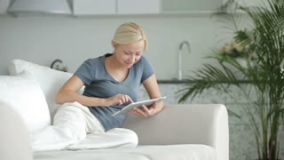 Young woman sitting on sofa using touchpad and smiling