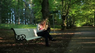 Young woman sitting on the bench in the park and using her laptop.