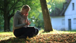 Young woman sitting on the ground outdoors with a laptop computer on her lap while chatting on her mobile phone to a friend backlit by the evening sun. Middle shot.