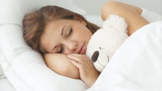Young woman sleeping in bed hugging teddy bear moving and smiling in sleep
