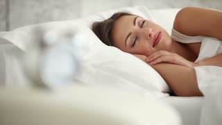 Young woman sleeping in bed opening her eyes and smiling at camera