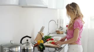 Young woman standing in kitchen cutting tomatoes and smiling at camera