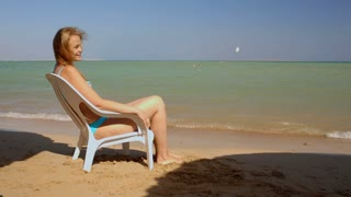 Young woman sunbathing sitting on the chair on the beach by the sea