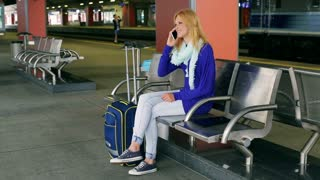 Young woman talking on cellphone and smiling to the camera on platform