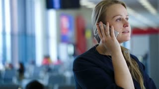 Young woman talking on the phone in the waiting room of airport or station, she giving information about her travel. Defocused interior in background