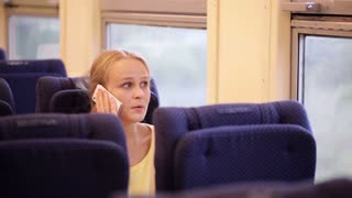 Young woman traveling by train and talking on the phone. After talk she is looking out the window