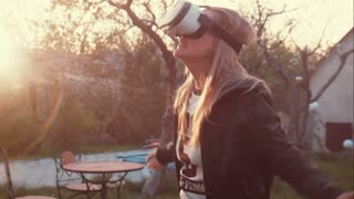 Young woman uses head-mounted display. Playing game using VR-helmet for smart phones.