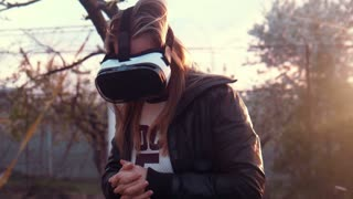 Young woman uses VR helmet with head mount display at home in the yard