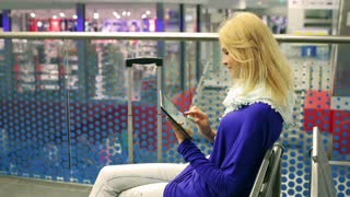 Young woman using tablet on the station and sitting on bench