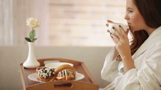 Young woman wearing bathrobe sitting on sofa drinking tea looking at camera and smiling. Panning camera
