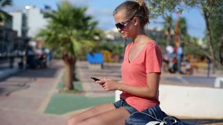 Young woman with cellphone in the park, steadycam shot