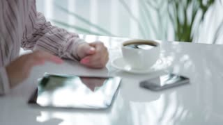 Young woman with cup of coffee and mobile phone in front of her using touchpad