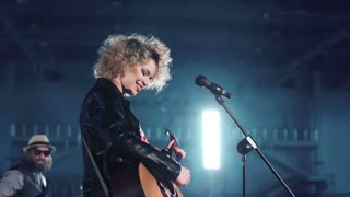 Young woman with curly hair wearing leather jacket and red checked shirt singing and playing guitar standing at microphone stand. Man band member with guitar sitting blurred in background