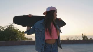 Young woman with longboard during sunset or sunrise in park, dolly shot, slow motion