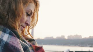 Young woman with red hair curls sitting in a scarf and using phone at the seacoast