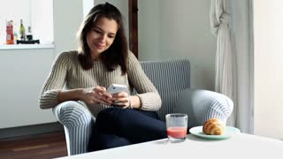 Young woman with smartphone sitting in armchair at home