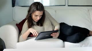 Young woman with tablet computer lying on sofa