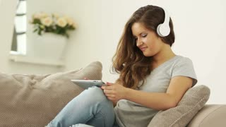 Young woman with tablet listening music
