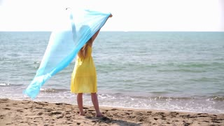 Young woman with waving sarong at the beach