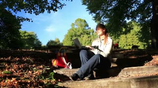 Young woman working outdoors on a laptop computer sitting on steps in the garden in late evening sunlight, enjoying the peace of nature