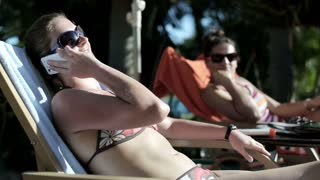 Young women lying on sunbed and talking on cellphone
