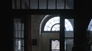 Zoom out arched window frame to wheelchair in tiled hall.