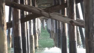 Zoom out of waves crashing under the dock