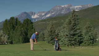 Zoomed Shot Of Man Teeing Off On Golf Course With Snowy Mountains Indistance