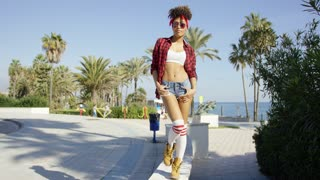 Adorable african american girl walking on concrete wall near to sea promenade. She wearing short sexy jeans checkered red shirt and bandana.
