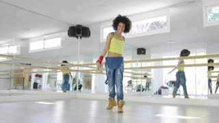 Adorable african american girl with huge afro haircut dancing hip hop in studio. She wearing large baggy jeans and work boots.