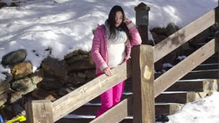 Adorable asian girl standing on wooden stairs in mountain snowy resort. She wearing snowboarder clothes.