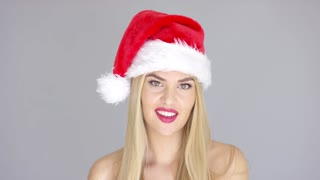 Adorable beautiful girl posing isolated in Santa Claus Hat on gray backround. She smiling to the camera. Bare shoulders.