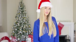 Adorable blond girl in christmas santa claus hat standing in decorated living room with chimney at her home.