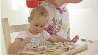 Adorable female toddler watching unidentifiable woman sift sugar as it falls on freshly baked muffins in wooden tray