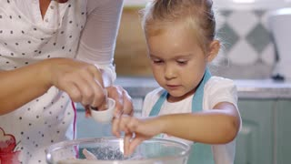 Adorable little girl adding salt to a baking mixture as she stands at the kitchen table with her Mum learning to bake