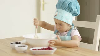 Adorable single toddler in large blue baking hat mixing a muffin batch with wooden spoon. Small dishes with ingredients on table.