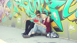 Affectionate hipster urban couple relaxing in town sitting on a sidewalk arm in arm looking at a tablet in front of colorful graffiti