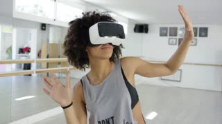 African american girl using VR glasses while dancing in modern mirrored studio.