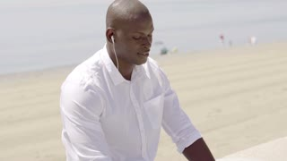 African man listening to music at the beach