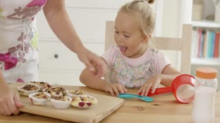 Arm of unidentifiable woman placing wooden tray of freshly bake muffins in front fascinated of child