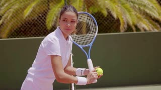 Athlete with ball and racket beside green wall practicing her tennis moves under a bright summer sun