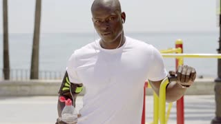 Athlete with uncapped sports bottle in park