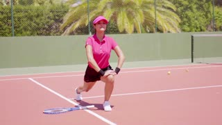 Athletic young woman doing stretching exercises on an all weather tennis court to warm up before playing a match