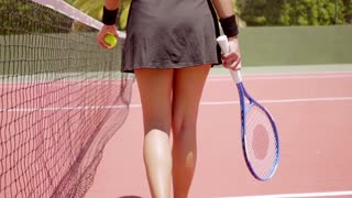 Athletic young woman tennis player walking away from the camera with a ball in her hand low angle view of her lower body