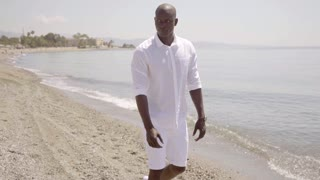 Attractive African man walking along a beach