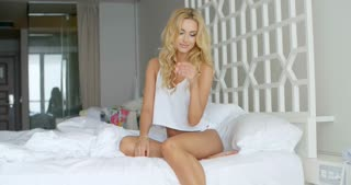 Attractive Blond Woman Sitting on White Bed