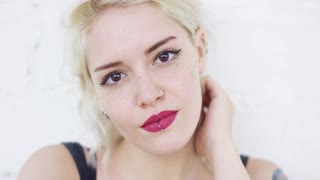 Attractive blond woman with a lip piercing wearing red lipstick smiling quietly at the camera close up frontal head and shoulders